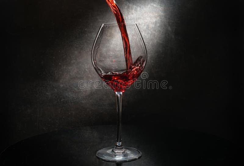 Pouring red wine. In dark vineyard royalty free stock photos