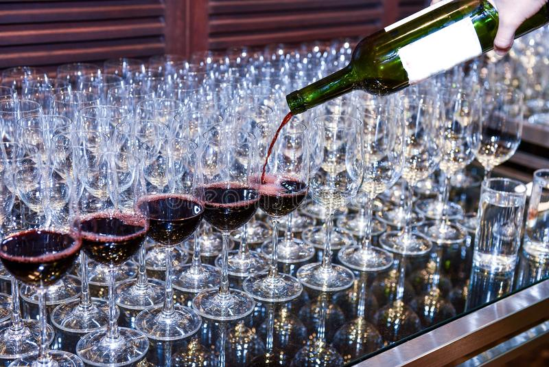 Pouring red wine to glasses for serving. Pouring red wine from bottle into the wineglass on row of glasses. Close up of red wine to service winery to party or royalty free stock images