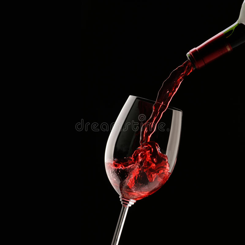 Pouring red wine into wine glass. On a black background royalty free stock images