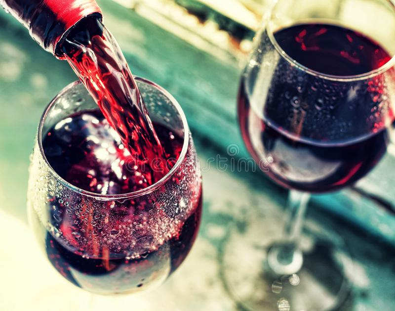 Pouring red wine. Wine in a glass, selective focus, motion blur,. Red wine in a glass. Sommelier pouring the wine into the glass. Thanksgiving Day, Valentine`s royalty free stock photography
