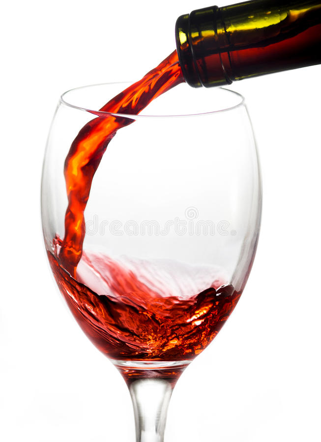 Pouring red wine into wine glass. Pouring red wine into white glass the white background stock images