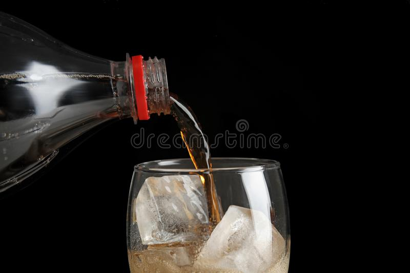Pouring refreshing cola from bottle into glass with ice cubes on black background. Closeup royalty free stock image