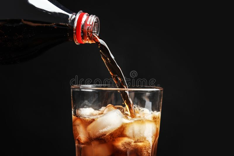 Pouring refreshing cola from bottle into glass with ice cubes on black background. Closeup stock images