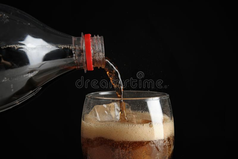 Pouring refreshing cola from bottle into glass with ice cubes on black background. Closeup royalty free stock photos