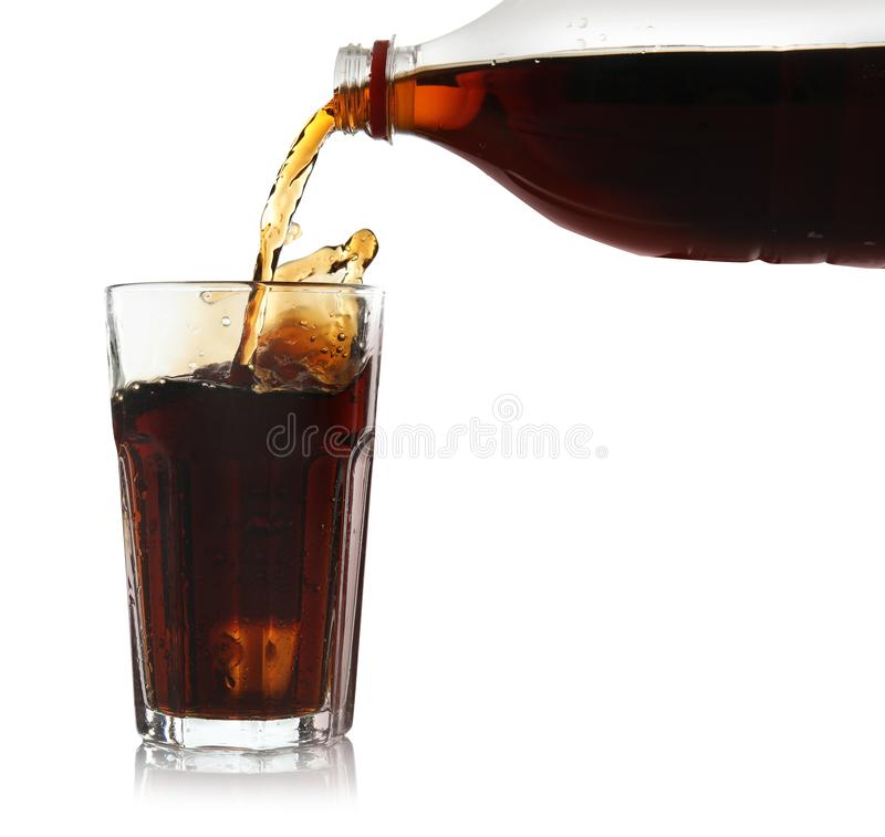 Pouring refreshing cola into glass. On white background stock images