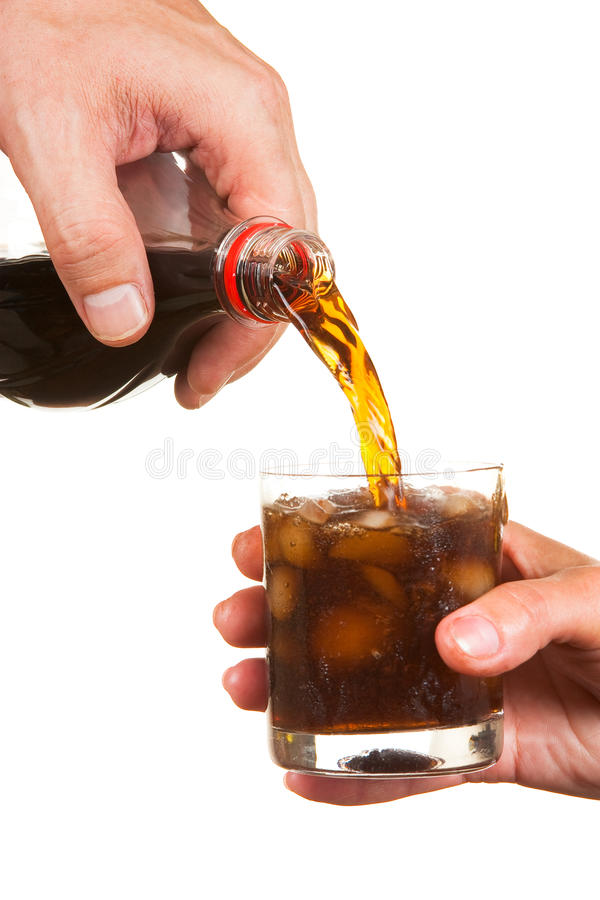 Pouring soda into a glass. Isolated on white background stock photography