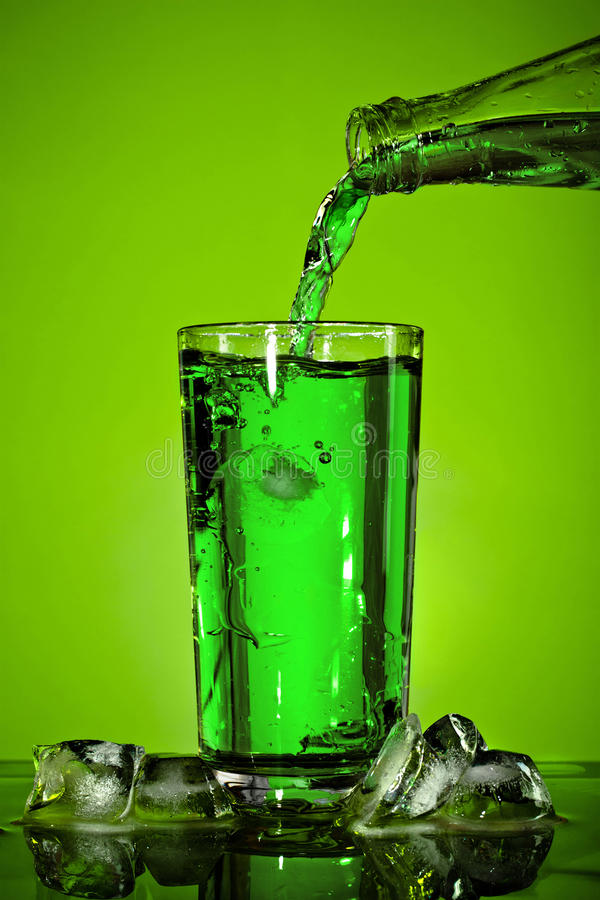 Pouring Soda. In glass over green background stock photo