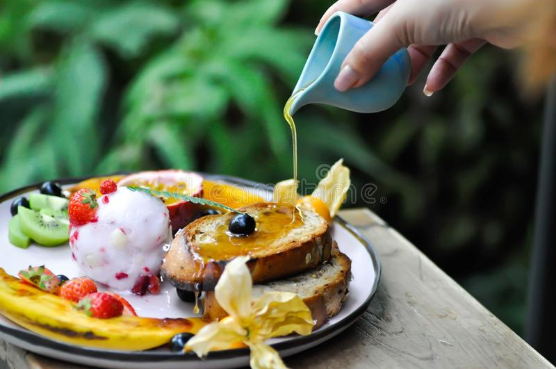 Pouring honey to berry ice cream with fruit and toast. Pouring some honey to berry ice cream with fruit and toast stock images