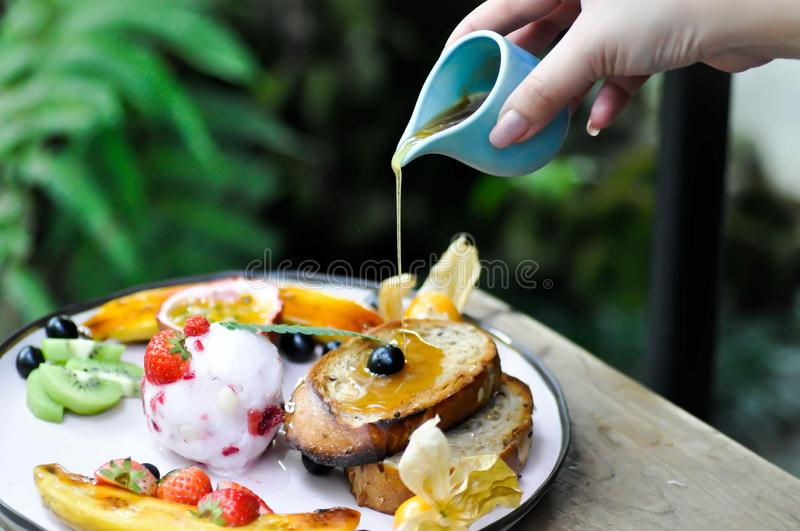 Pouring honey to berry ice cream with fruit and toast. Pouring some honey to berry ice cream with fruit and toast royalty free stock photo