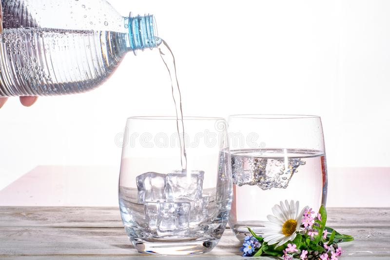 Pouring of sparkling soda mineral drink water in glasses with ice cubes close up copy space stock photo