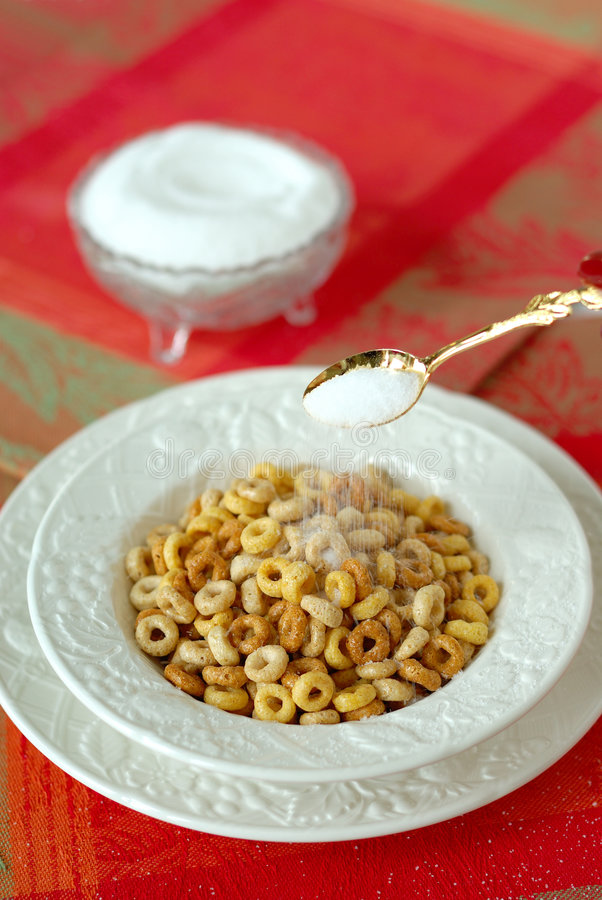 Pouring A Spoonful of Sugar on Multi-grain Cereal in a White Chi stock image