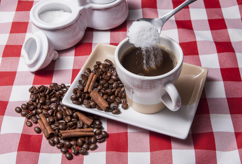 Pouring sugar into cup of coffee. stock photos