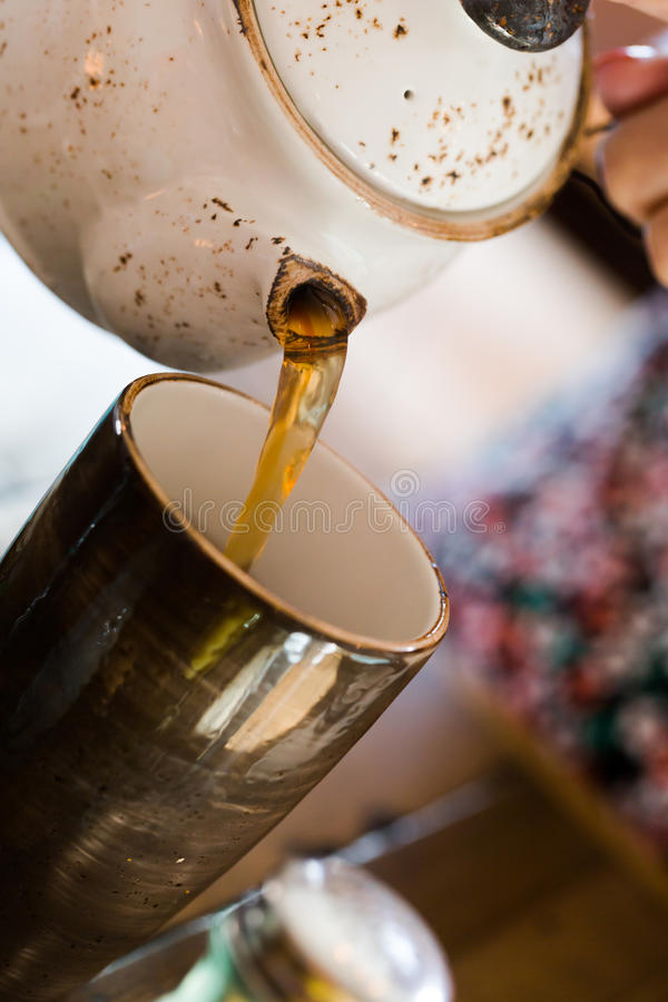 Pouring tea into clay cup from earthenware tea pot royalty free stock photography