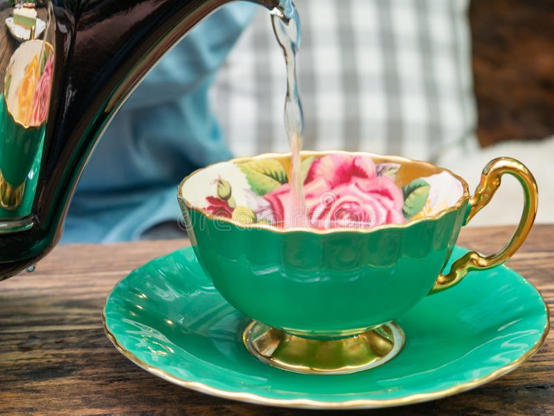 Pouring a tea into a green cup. Side view of a female pouring tea royalty free stock images