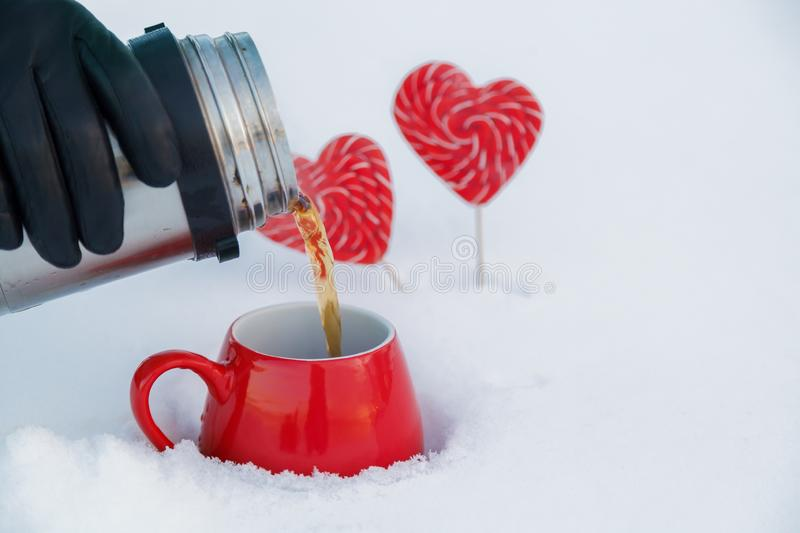 Pour tea from a thermos into a red mug in the fresh air on a picnic on Valentine`s day on the background of candy hearts stock photo