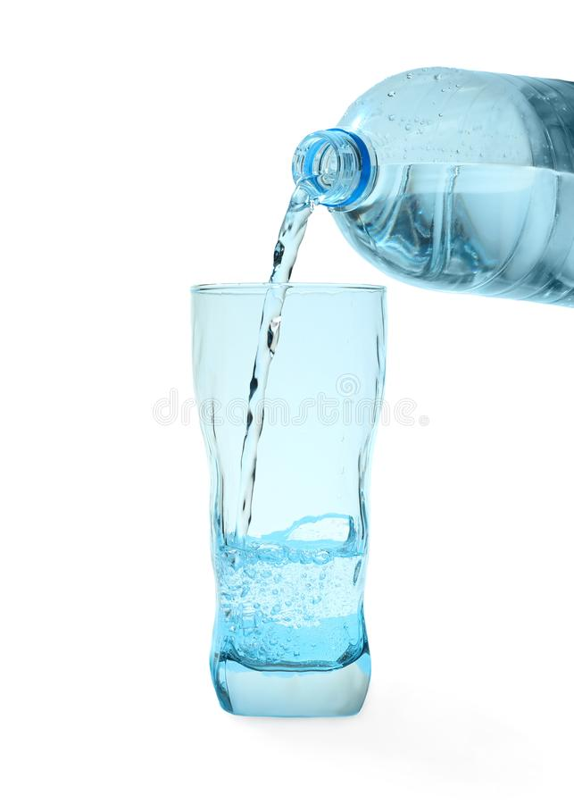 Pouring water from bottle into glass against blue background stock photography