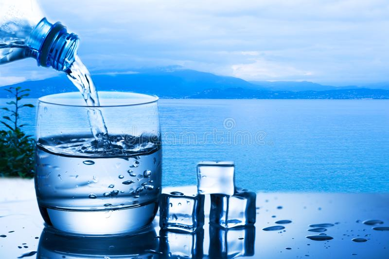 Pouring water from bottle into a glass against the nature background with lake and plant near ice cubes stock photo
