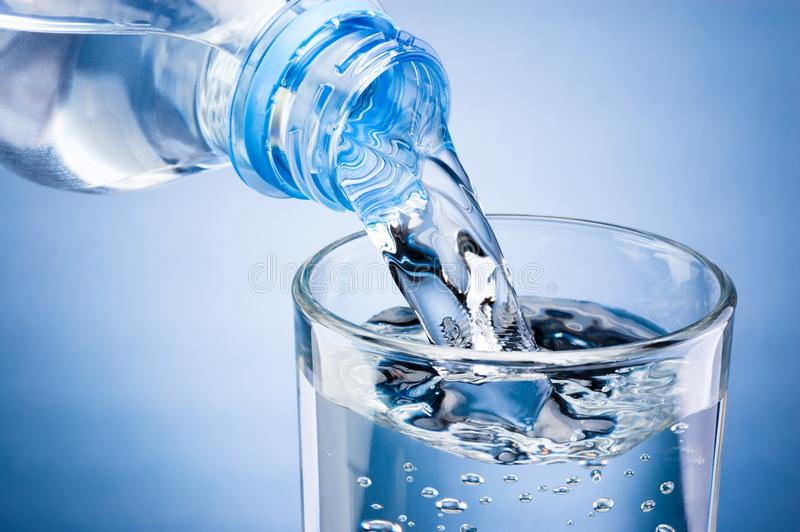 Pouring water from bottle into glass on blue background royalty free stock photo