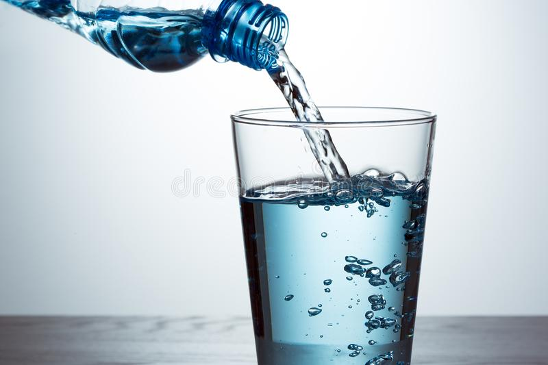 Pouring water from bottle into glass. Pouring blue water from bottle into glass stock photography