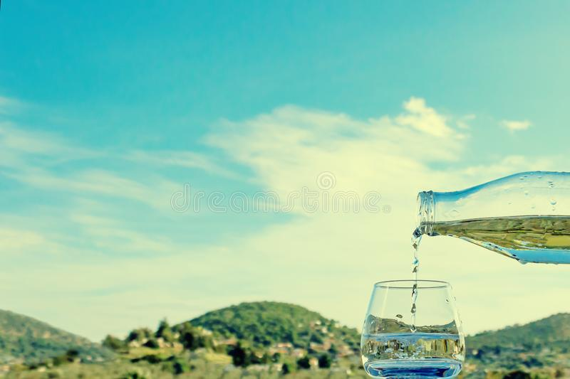 Pouring water into a glass against the nature landscape. royalty free stock photos