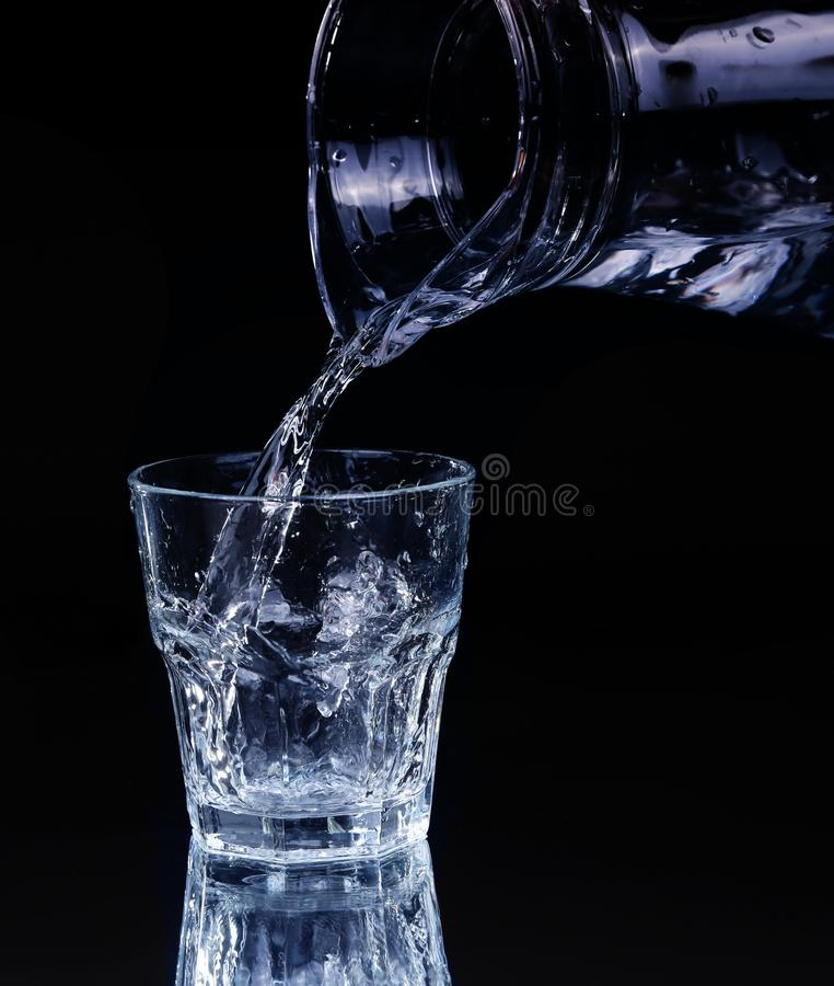 Pouring water on a glass on black. Background royalty free stock images