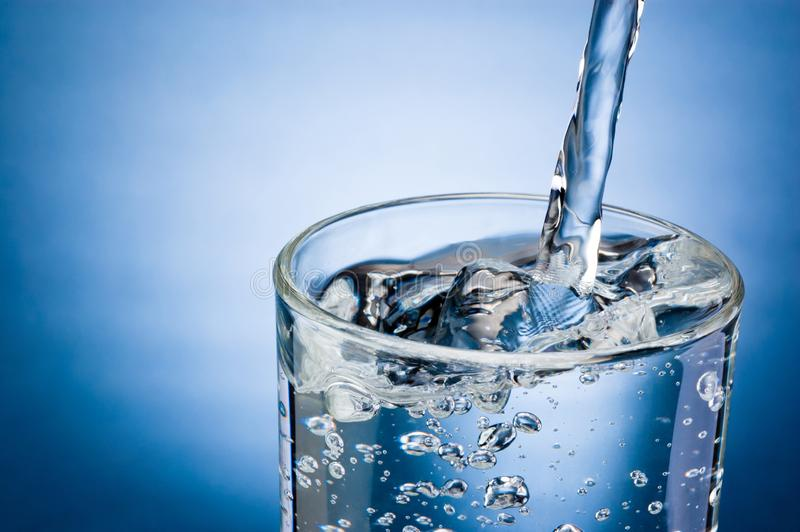 Pouring water into glass on blue background stock images