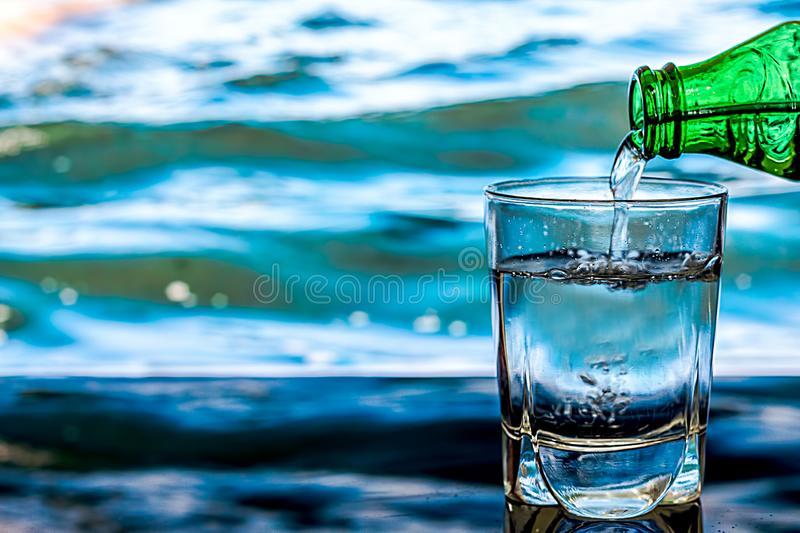 Pouring water into glass on blue background. stock photography