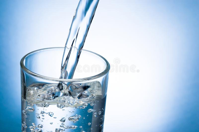 Pouring water into glass on blue background royalty free stock photography