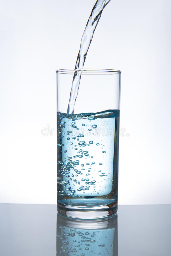 Pouring water into glass stock image