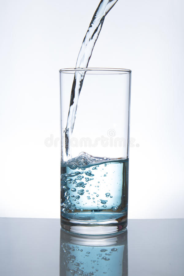 Pouring water into glass. Concept of drinking. Pouring water from into glass stock photos