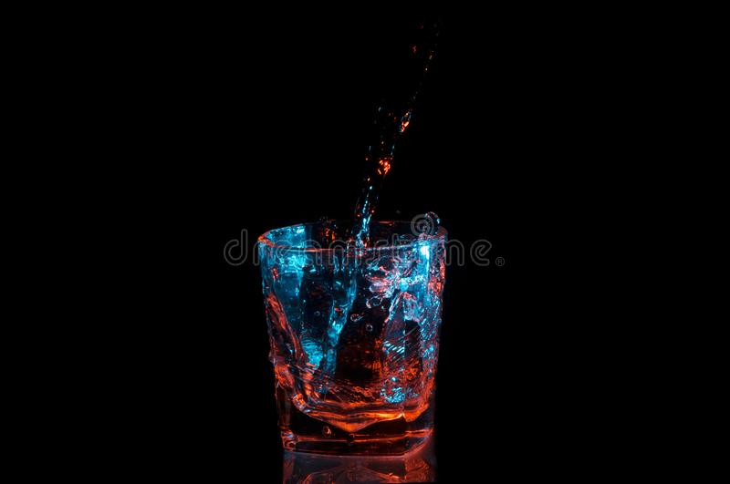 Pouring water into a rocks glass under blue and orange lights isolated on a black background royalty free stock images