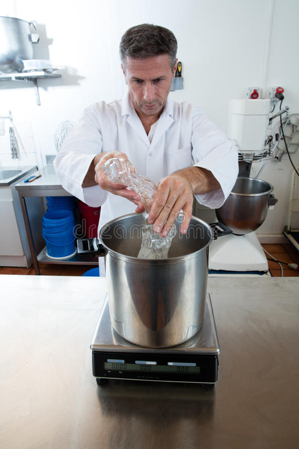 Pouring and weighting glucose on industrial scale for sweet specialty. Male professional with white lab coat pouring and weighting glucose on industrial scale stock photos
