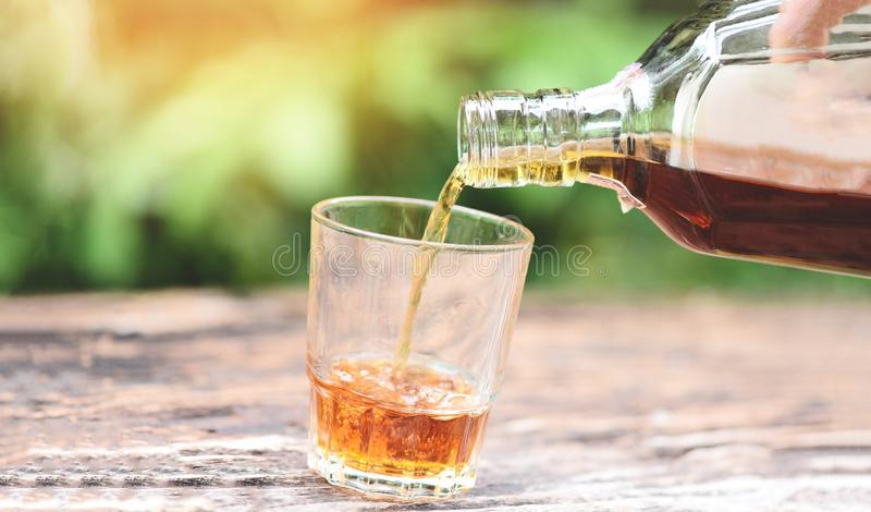Pouring whiskey or alcohol drink from bottle to glasses on wooden  background / Pour liquor. Pouring whiskey or alcohol drink from bottle to glasses on wooden stock photo