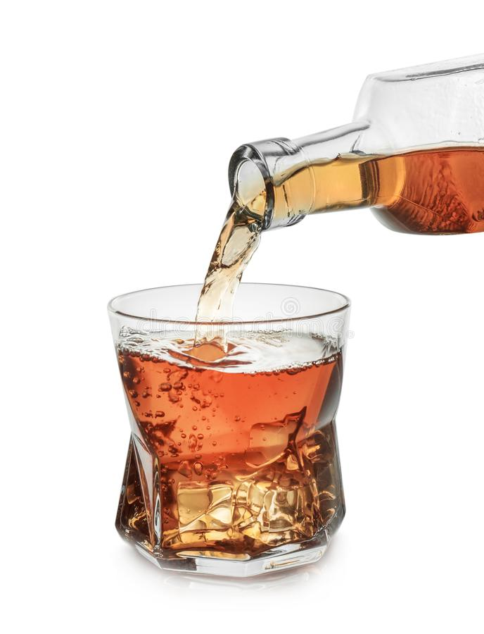 Pouring whiskey from bottle into glass with ice cubes on white background stock images