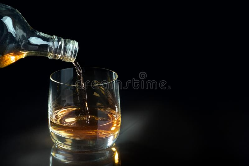 Pouring whiskey into glass. Free space for text, dark background royalty free stock photo