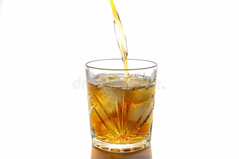 Pouring whiskey in a glass with ice. front view. Isolated royalty free stock image