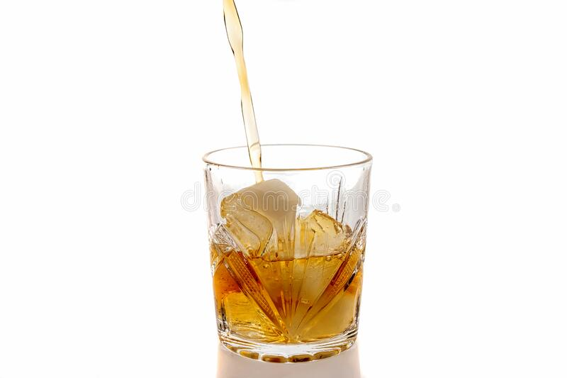 Pouring whiskey in a glass with ice. Front view. Isolated stock photo