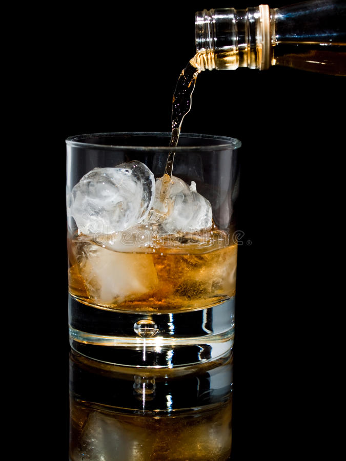 Pouring whisky with ice on black background. A glass tumbler with ice cubes being filled with whisky, with reflection, on black stock photography