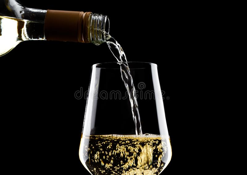 Pouring white wine from bottle to glass on black stock images