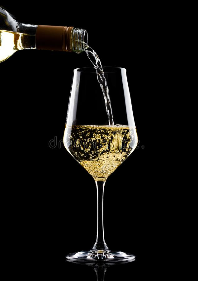 Pouring white wine from bottle to glass on black stock photography