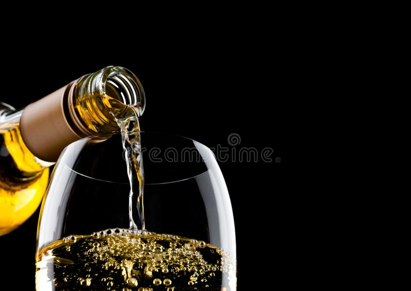 Pouring white wine from bottle to glass on black with space for your text stock images
