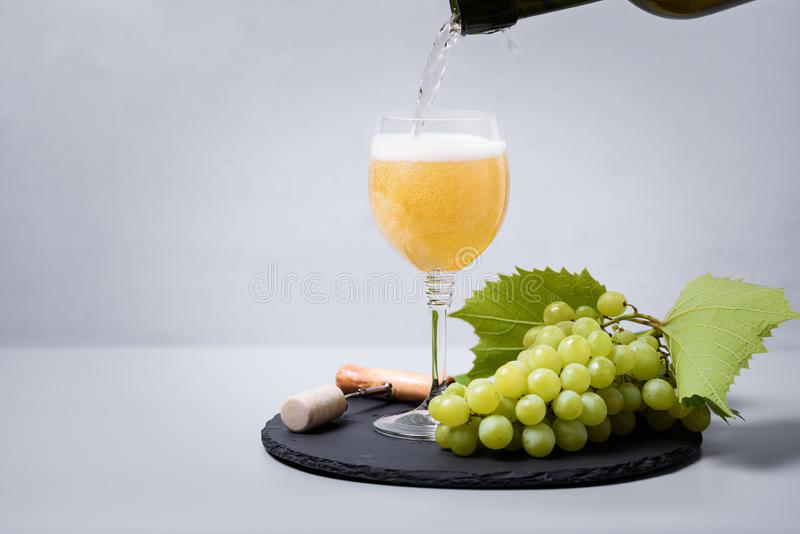 Pouring white wine champagne from bottle into wineglass on gray background. Holiday celebration concept royalty free stock images