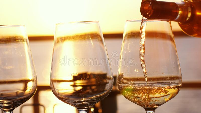Pouring white wine in glasses at amazing sunset with sea view in beach restaurant. Pour white wine in glasses at sunset by the sea in beach cafe royalty free stock photography