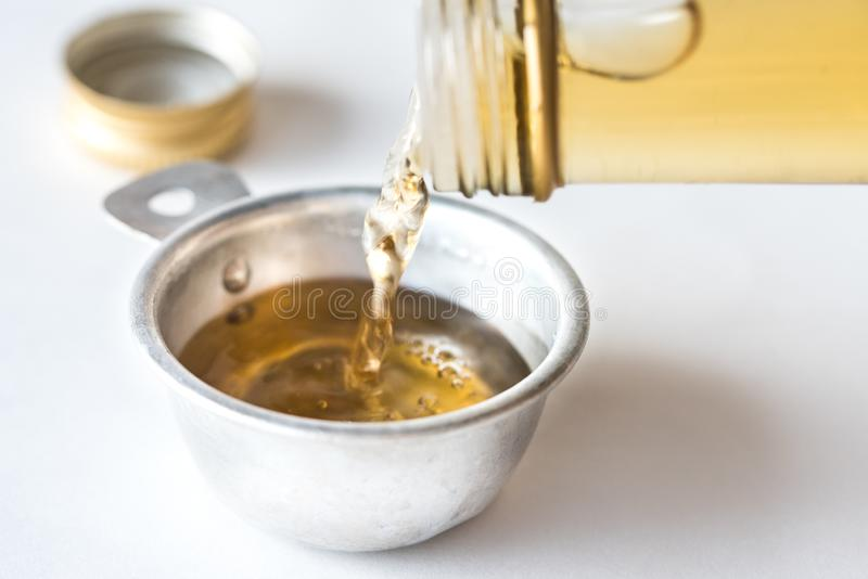 Pouring White Wine Vinegar into a Measuring Cup stock photography