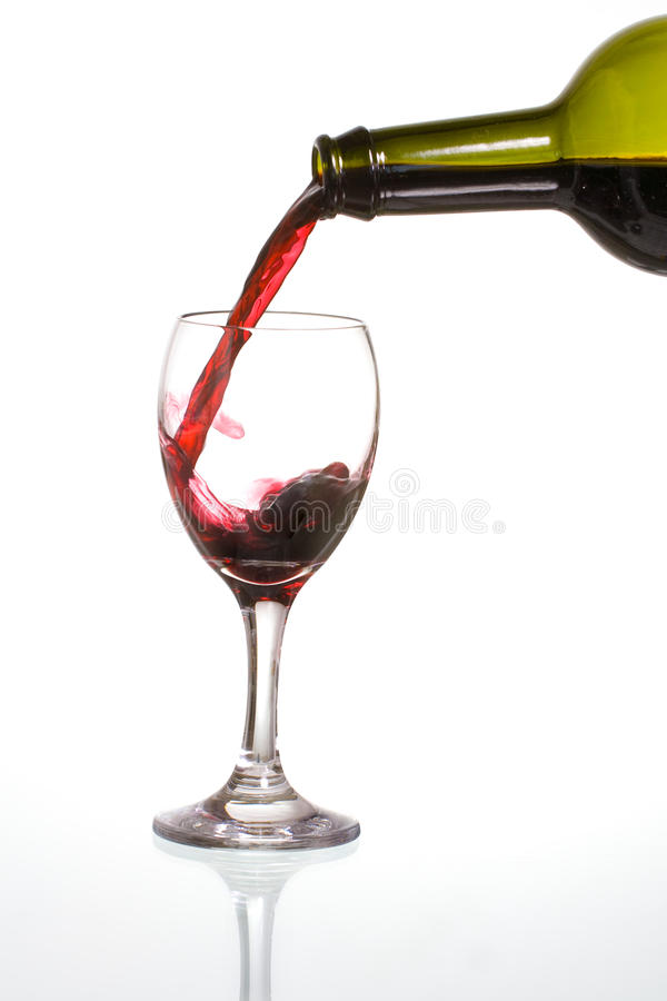 Pouring wine. Pouring delicious red wine in a glass with reflection stock images
