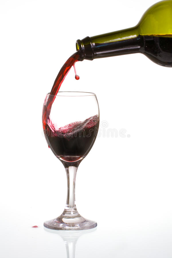 Pouring wine. Pouring delicious red wine in a glass with reflection royalty free stock photo