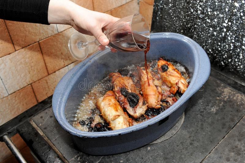 Pouring wine on chicken specialty with plums royalty free stock photos