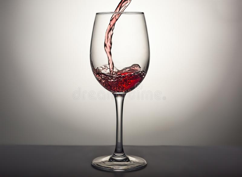 Pouring, wine, glass, red wine, Valentine`s Day, alcohol, splash, luxury, gourmet. Pouring wine into a glass. Red wine. Valentine`s Day, birthday, date royalty free stock photos