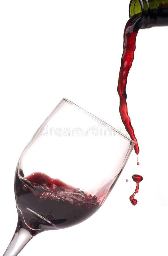Pouring Wine into Glass on White. Pouring wine into wine glass on white background royalty free stock photography