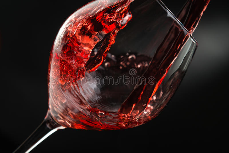 Pouring wine. Pouring red wine, dark background royalty free stock photos